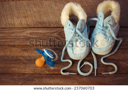 2015 year written laces of children's shoes and a pacifier on the old wooden background. Toned image  - stock photo
