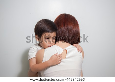 3 years old Asian kid hugging his mother on white background - stock photo