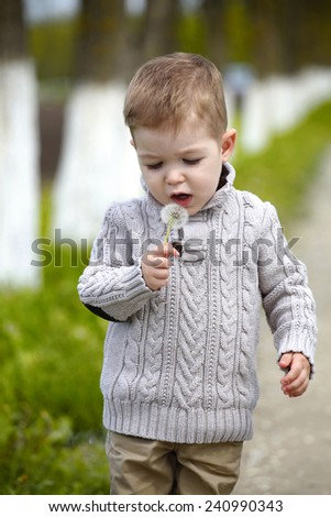 2 years old Baby boy with dandelion in spring park - stock photo