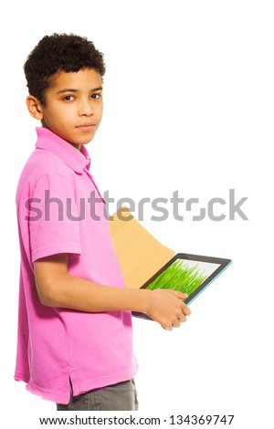 10 years old black boy standing with tablet pc, waist up portrait  (image on tablet from photographers portfolio) - stock photo