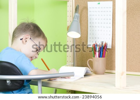 5 years old boy doing his homework - education - stock photo