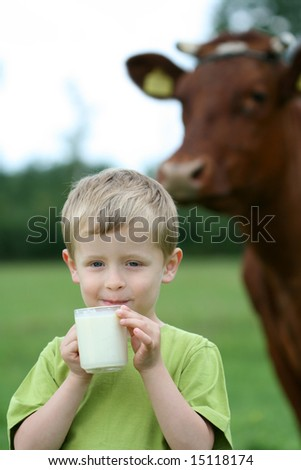 4-5 years old boy drinking milk on farm - stock photo