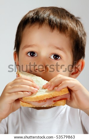 4 years old boy eating white bread sandwich (sandwich and studio lights reflected in eyes) - stock photo