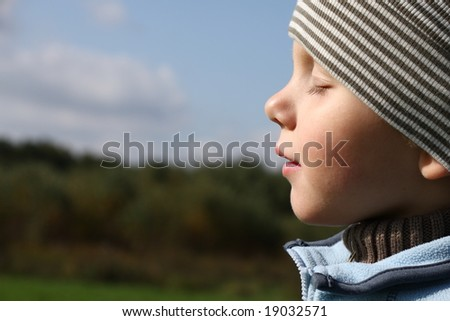 3 years old boy enjoying sun in autumn - stock photo