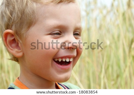 3 years old boy laughing on a wheat field - stock photo
