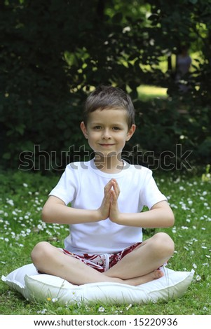 6 years old boy meditating outdoor - stock photo