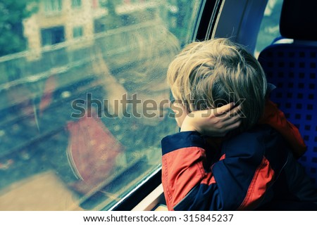 7 years old boy sitting in the train and looking to the rain - stock photo