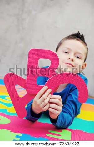 9 years old boy with alphabet letters - kids and family /focus on letters/ - stock photo