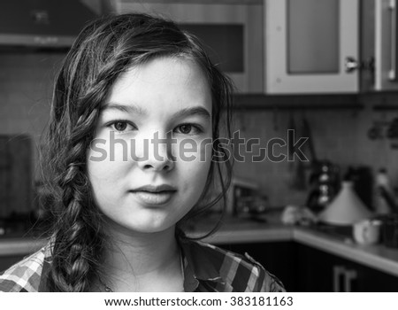 9-10 years old brunette girl in the interior of her room.  Black and white photo - stock photo