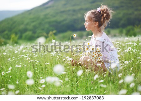 7 years old child having fun in flower field - stock photo