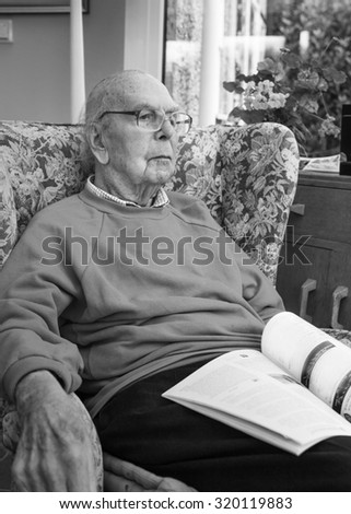 95 years old English man sitting in chair in domestic environment. Health and care concept  - stock photo