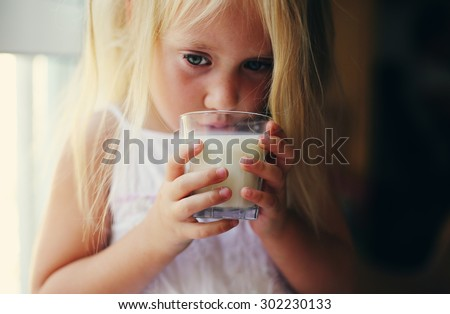4 years old girl holding glass of milk - stock photo