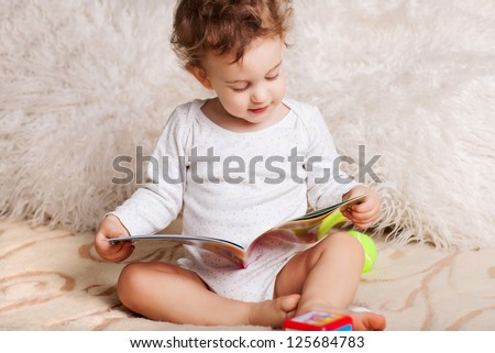 2 years old happy baby boy sitting on sofa reading story book and smiling. - stock photo
