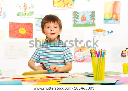 3 years old happy boy cutting cardboard with scissors in the art preschool class - stock photo