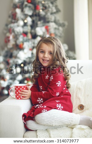 5 years old little girl drinking milk near Christmas tree in morning at home - stock photo
