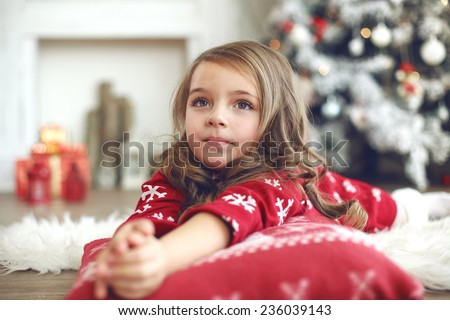 5 years old little girl laying down on soft cushion near Christmas tree at home - stock photo
