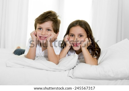 7 years old little girl posing on bed or couch together with her 4 years old small brother smiling happy in brotherhood and children lifestyle concept - stock photo
