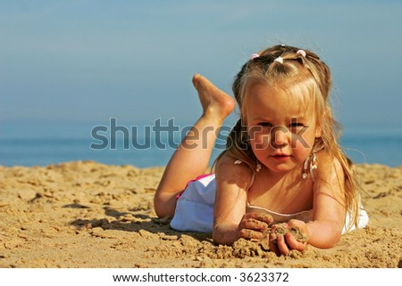 3 years old little girl relaxing and playing with sand on a beach - stock photo