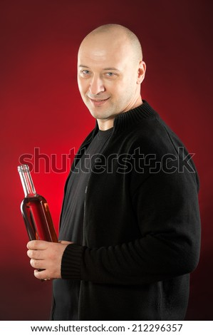 38 years old man holding bottle of Rose wine against red background wearing black clothes  - stock photo