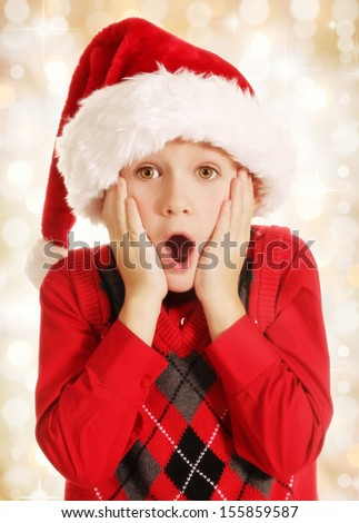 7 years old surprised boy in Santa hat Christmas portrait on lights background - stock photo