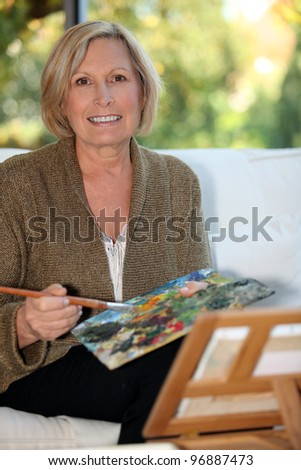50 years old woman painting - stock photo