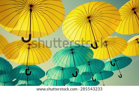yellow and blue umbrellas under the beautiful cloudy sky. color - stock photo