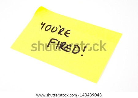 'You're Fired!' written on a yellow sticky note - stock photo