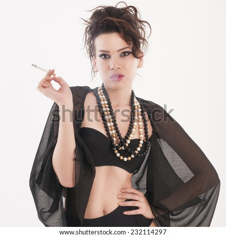 Young adult erotic girl in underwear smoking tobacco - stock photo