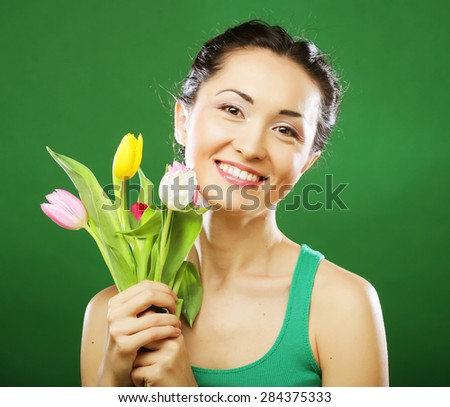 young asian woman holding a bouquet of tulips over green background - stock photo