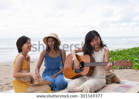 young asian woman playing guitar on sea beach - stock photo