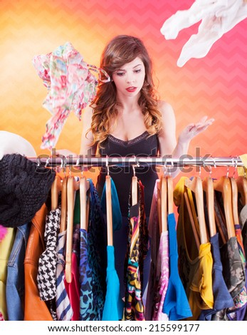 Young attractive woman searching for clothing in a closet  - stock photo