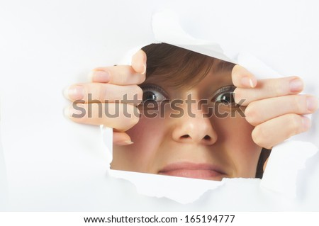 Young beautiful curious woman looking through the hole in paper - stock photo
