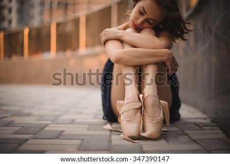 young beautiful modern style ballet dancer sitting on the ground in black dress . selective focus. Concept of romance, tenderness - stock photo