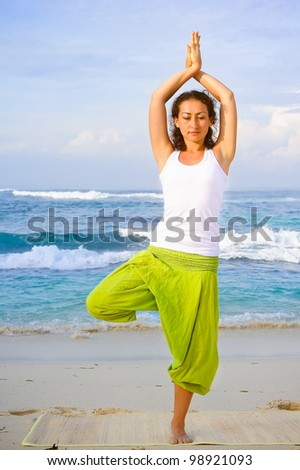 Young beautiful woman making yoga on the beach - stock photo