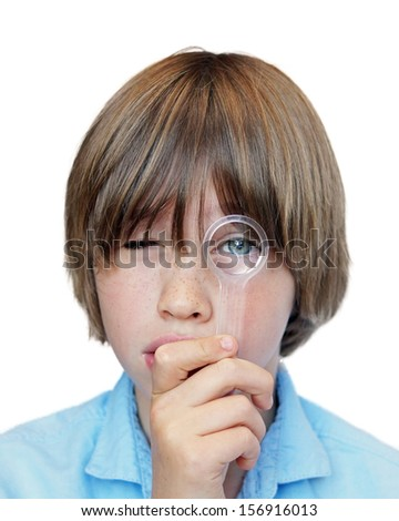 Young boy looking directly at camera with one eye looking through a magnifying glass                           - stock photo