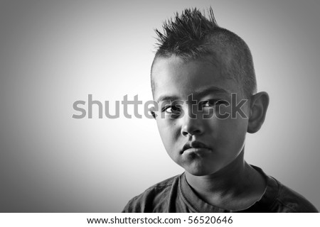Young boy with funny mohawk haircut and serious look in black and white - stock photo