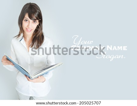 Young brunette wearing a white shirt reading a book  - stock photo