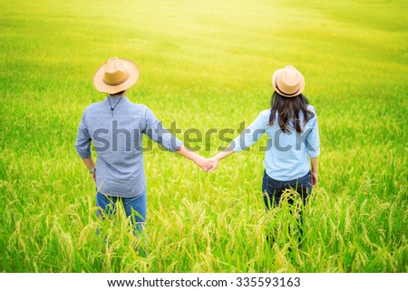 Young Couple holding hands in green rice fields at sunset - stock photo