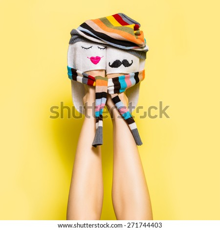 Young couple in love concept. Funny woman legs in slippers over yellow. One hat and scarf for two, happy together concept. soft studio shot - stock photo