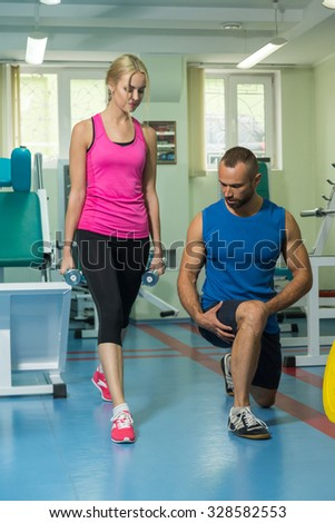 Young couple in the gym. Mutual support and assistance in the exercises. Work on your body. Photos for sporting and social magazines and websites.  - stock photo