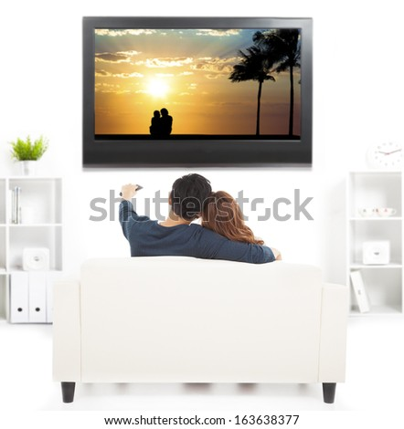 young couple on sofa watching TV with remote control - stock photo
