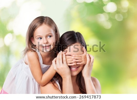 8. Young daughter closes hands eyes mom - isolated. Happy family people concept. - stock photo