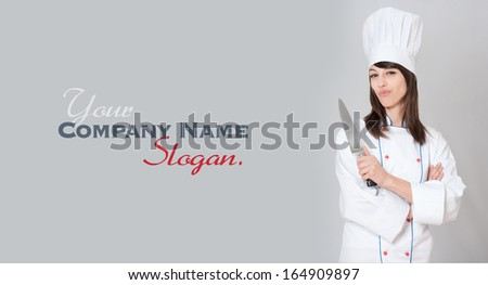 Young female chef holding a carving knife with a funny expression  - stock photo