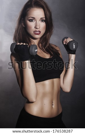 young fit woman lifting dumbbells on dark background - stock photo