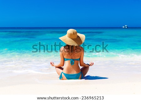 Young girl in a straw hat on a tropical beach. Summer vacation concept. - stock photo