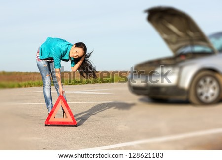young girl sets the warning triangle - stock photo