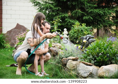 Young handsome father learning his small daughter to watering garden - stock photo