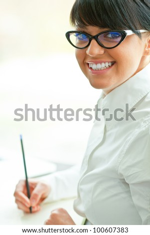 Young happy business woman writing some notes in the office . - stock photo