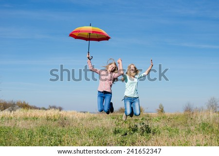 2 young happy teenage girls with colorful umbrella jumping high on empty autumn field copy space background - stock photo