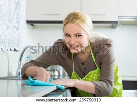 young housewife cleaning furniture in kitchen   - stock photo